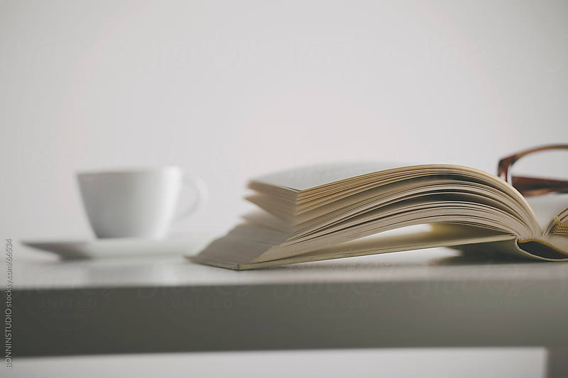 Book, glasses and coffee cup on the table. White background. by BONNINSTUDIO for Stocksy United