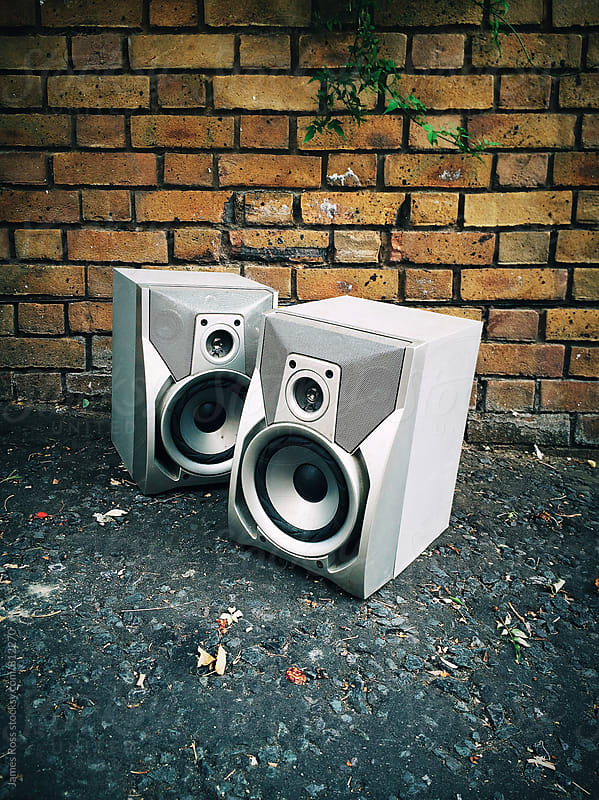 A pair of retro speakers on a pavement by James Ross for Stocksy United