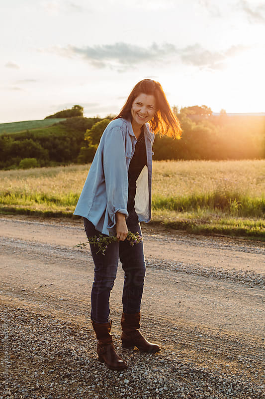 Laughing woman standing on countryside road at dusk by Carey Shaw for Stocksy United