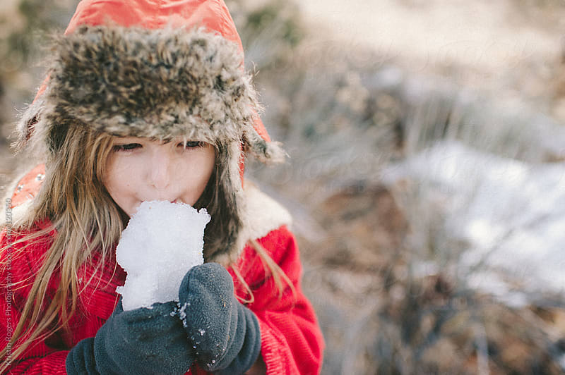 young girl eating snow with gloves on by Kristin Rogers Photography for Stocksy United