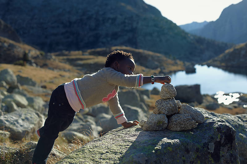 Little girl playing with rocks outdoors in the mountains by Miquel Llonch for Stocksy United