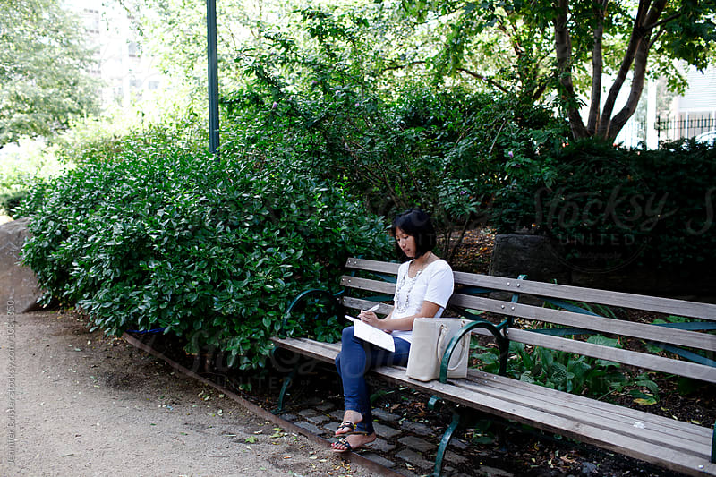 woman sitting in park, writing in notebook  by Jennifer Brister for Stocksy United