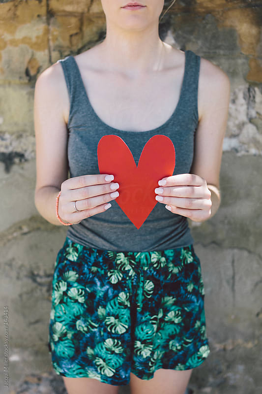 Teenage girl holds a red paper heart in front of her body by Jacqui Miller for Stocksy United