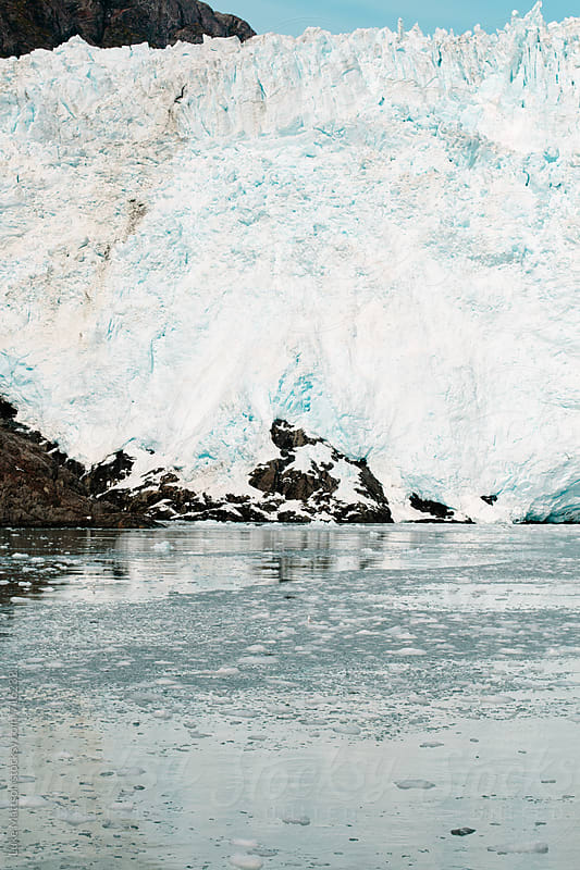 A Glacier Deposits Its Melting Ice Into Cold Ocean Waters by Luke Mattson for Stocksy United