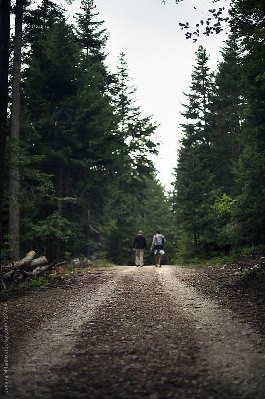 Two man walking trough the woods by Jovana Milanko for Stocksy United