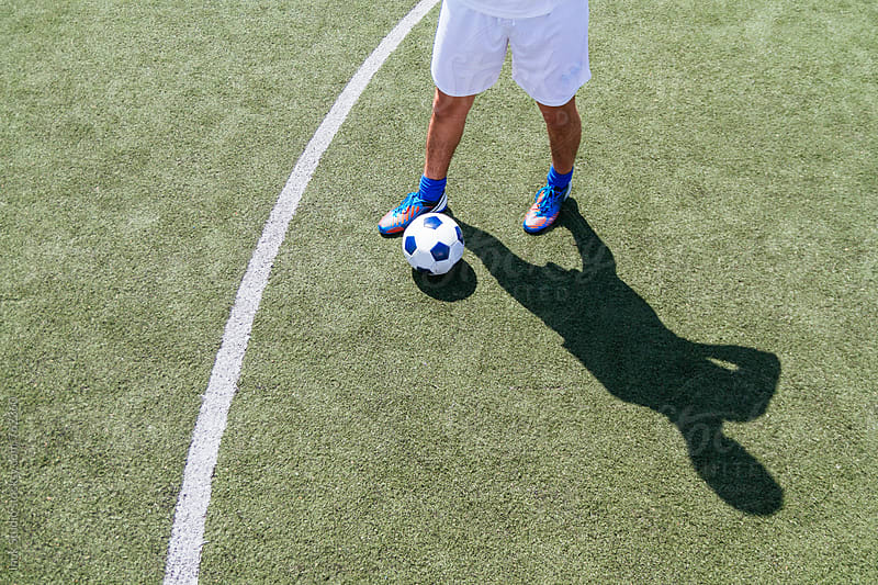 View of the legs of a soccer player and soccer ball in the field casting a shadow by Inuk Studio for Stocksy United
