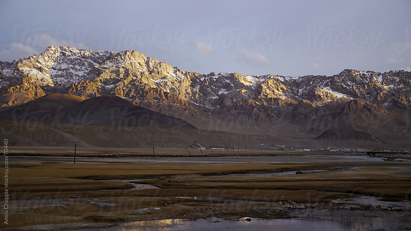 Pamir mountains caught in evening sunlight.  by Amos Chapple for Stocksy United