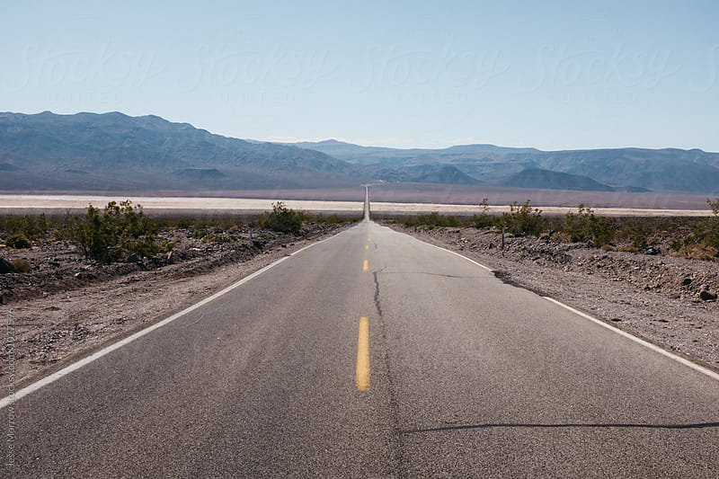 long road extending to mountains in distance  by Jesse Morrow for Stocksy United
