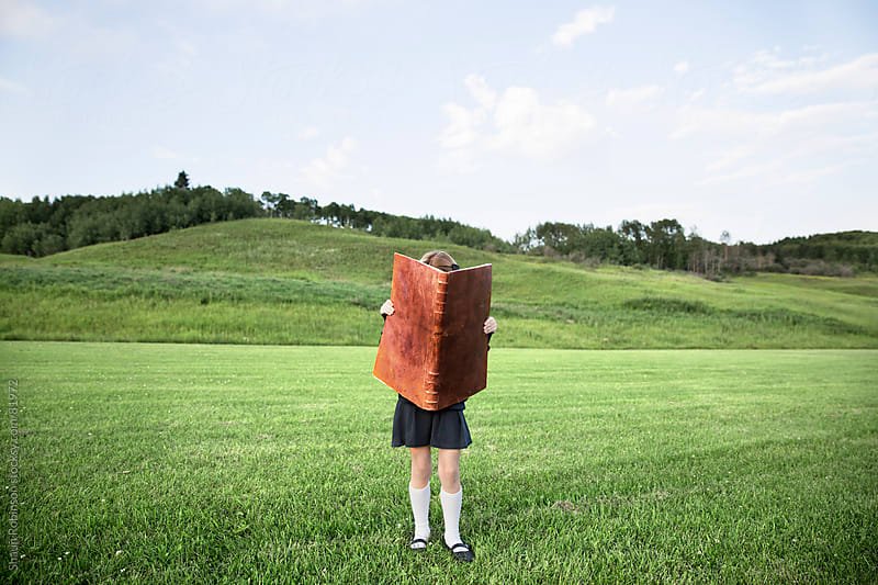 a girl in a uniform standing in a grass field with an oversized book by Shaun Robinson for Stocksy United