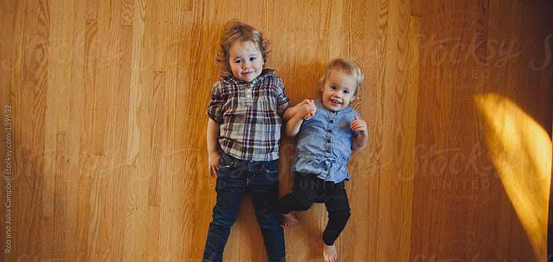 Cute toddler sisters lying on hardwood floors by Rob and Julia Campbell for Stocksy United