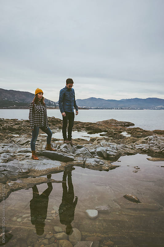 Young couple standing on coast. Cold spring day. La Costa Brava, Spain. by BONNINSTUDIO for Stocksy United