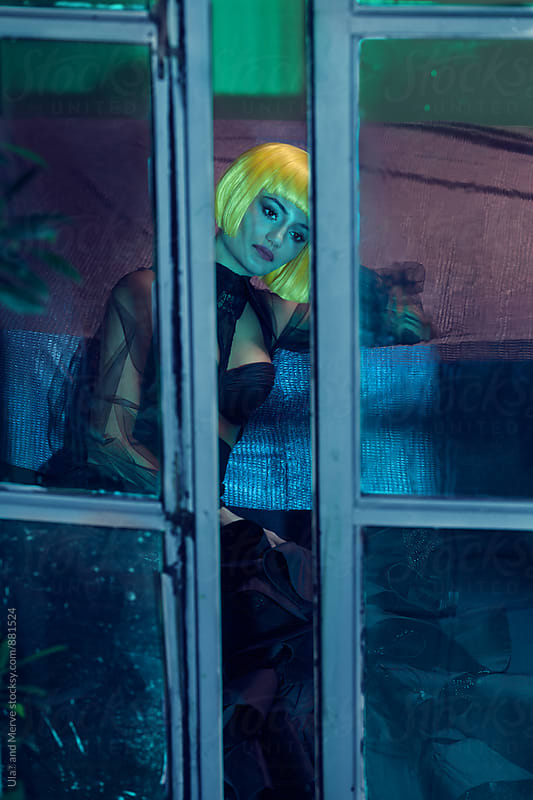 portrait of a lady with a wig in a moody room by Ulaş and Merve for Stocksy United