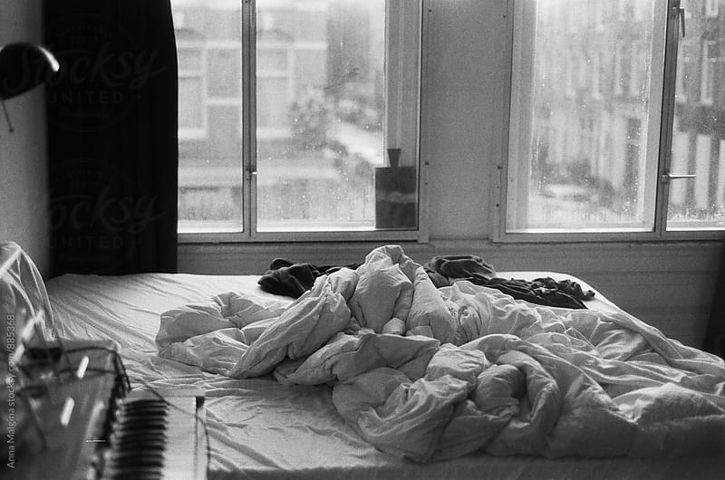 A black and white film photo of disordered bedroom with a piano by Anna Malgina for Stocksy United
