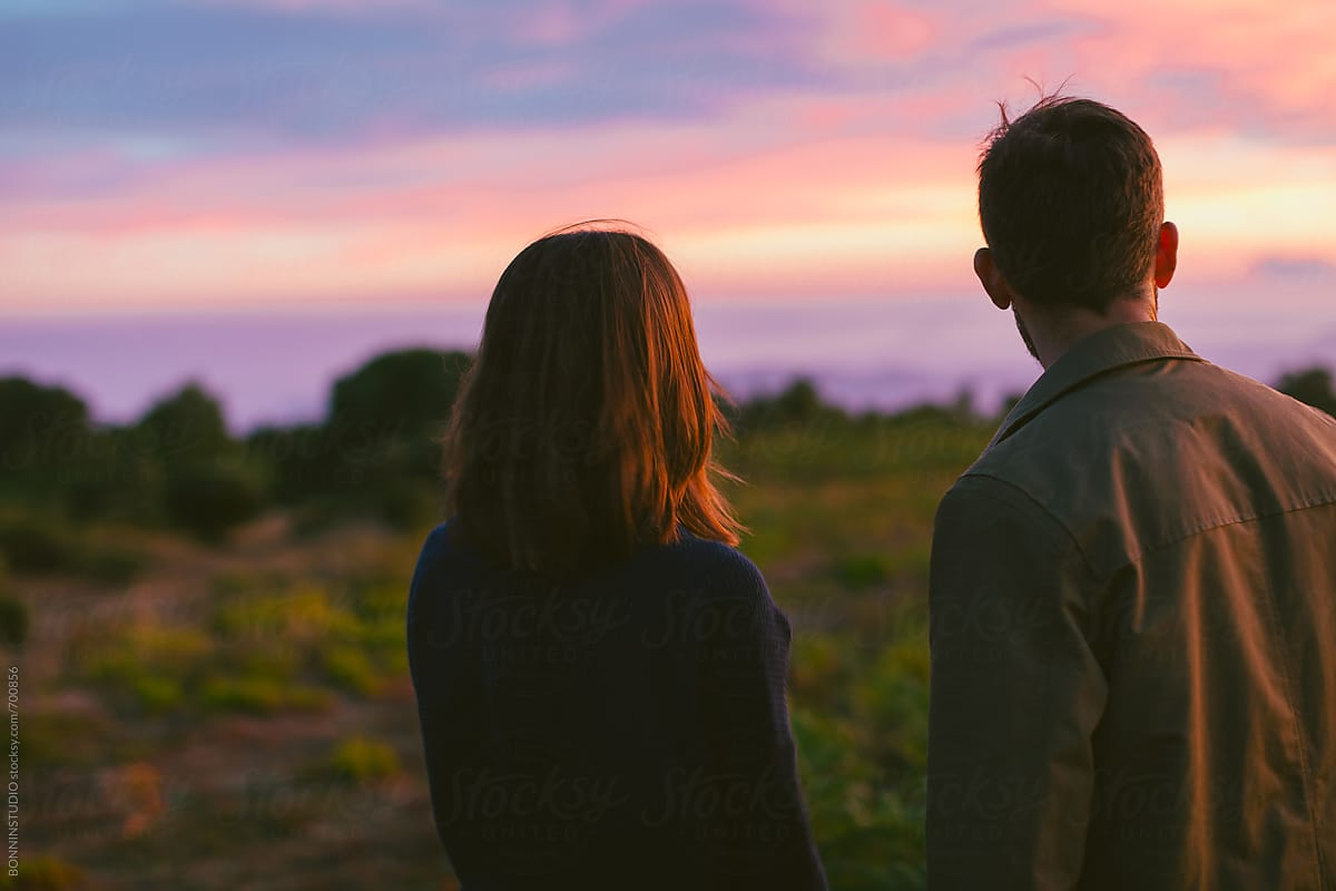 Back view of a young couple looking the beautiful sunset on the mountain. by BONNINSTUDIO  for Stocksy United