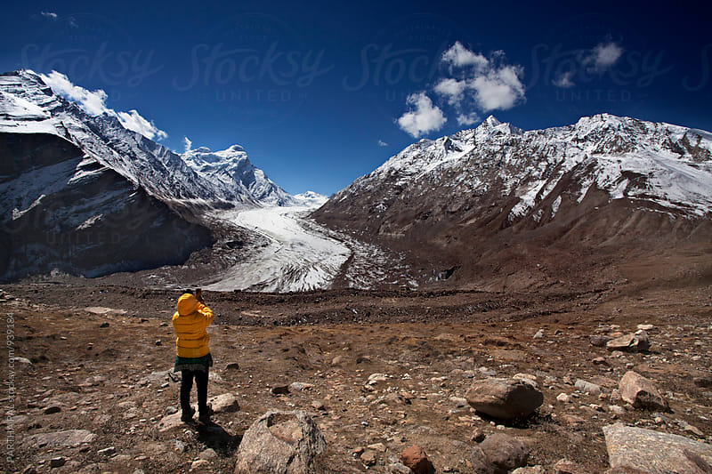 A woman using smartphone and capturing photograph of Glacier by PARTHA PAL for Stocksy United