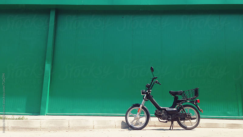 Old black motorcycle infront of green wall by Marko Milovanović for Stocksy United