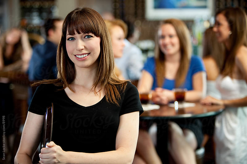 Bar: Cheerful Female Server with Customers Behind by Sean Locke for Stocksy United