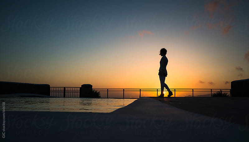 Woman walking against sunset by GIC for Stocksy United