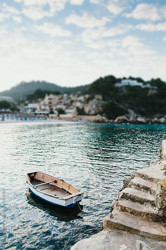 Small wooden dinghy moored near a flight of steps by Amir Kaljikovic for Stocksy United