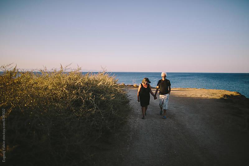 Old couple walking on the seacoast by Evgenij Yulkin for Stocksy United