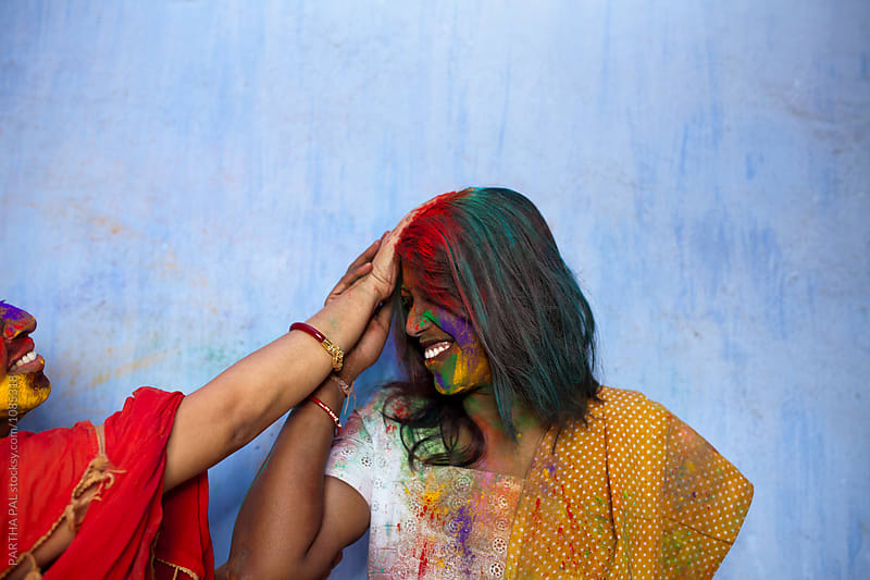 Indian woman giving spray color to other wonam by PARTHA PAL for Stocksy United