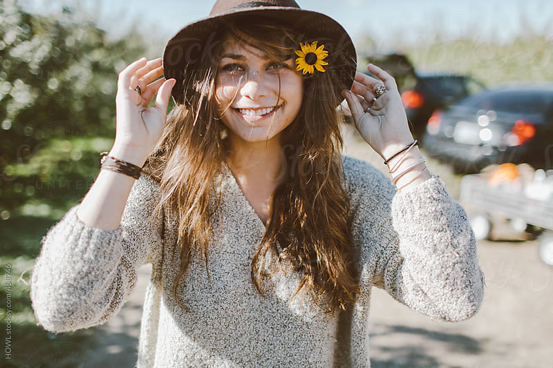 Beautiful young girl fixes her hat as she smiles to the camera  by HOWL for Stocksy United