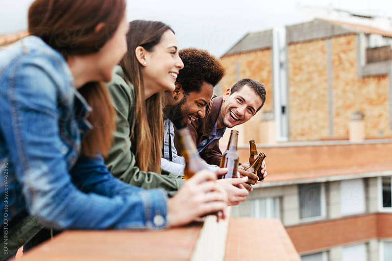 Group of friends having fun drinking beer on a rooftop. by BONNINSTUDIO for Stocksy United