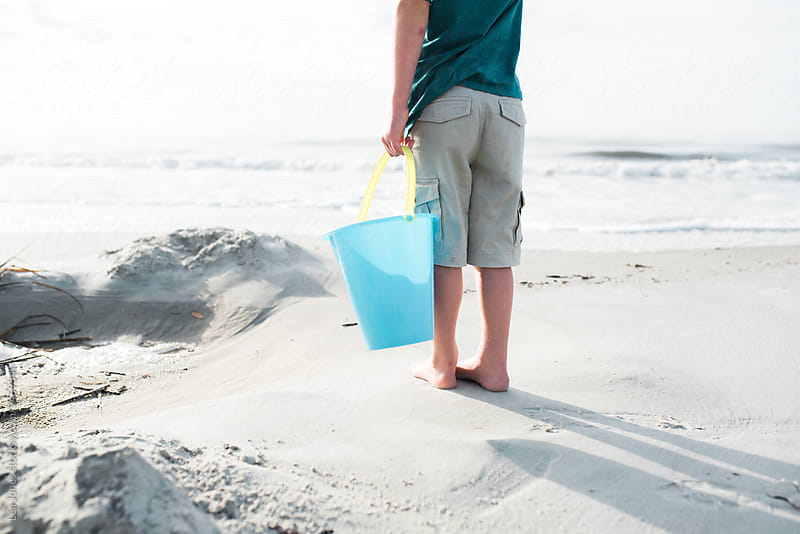little kid at the beach holding a bucket  by Léa Jones for Stocksy United