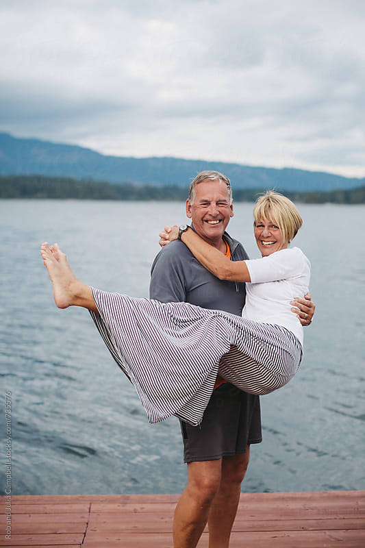 Mature couple looking at camera near lake - man holding woman in arms by Rob and Julia Campbell for Stocksy United