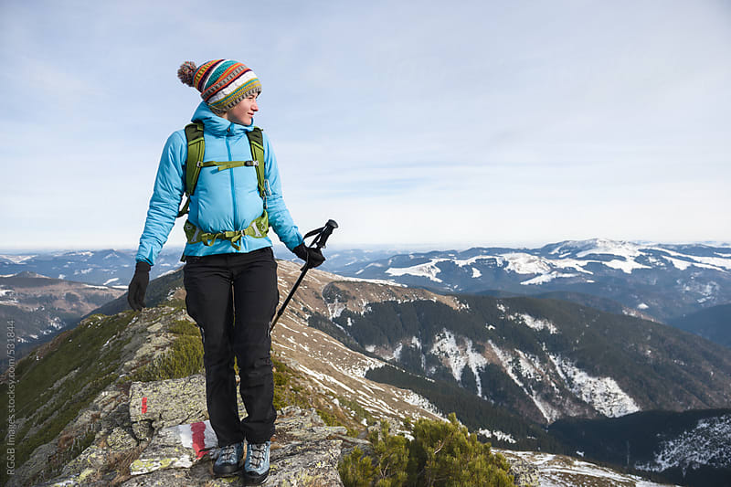 Woman hiking on top of a mountain ridge by RG&B Images for Stocksy United