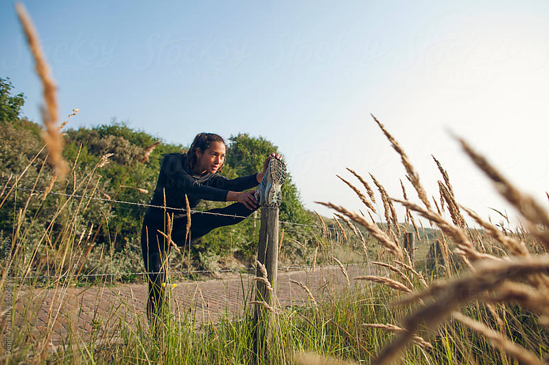 Woman stretching against a fence during her workout in the dunes by Denni Van Huis for Stocksy United