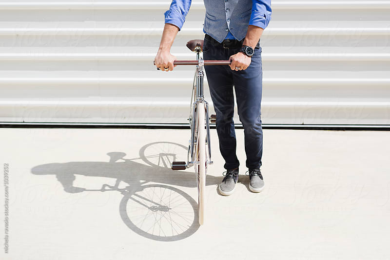 Man holding his stylish bicycle by michela ravasio for Stocksy United