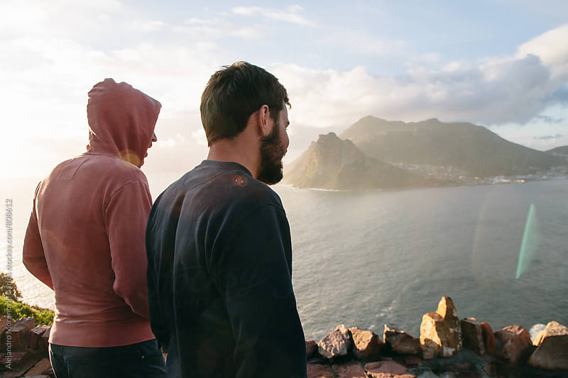 Back view of two young men friends on a lookout looking at the sea coast at sunset by Alejandro Moreno de Carlos for Stocksy United
