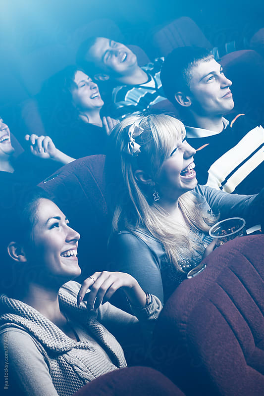 Group of friends watching movie in movie theater. by Ilya for Stocksy United