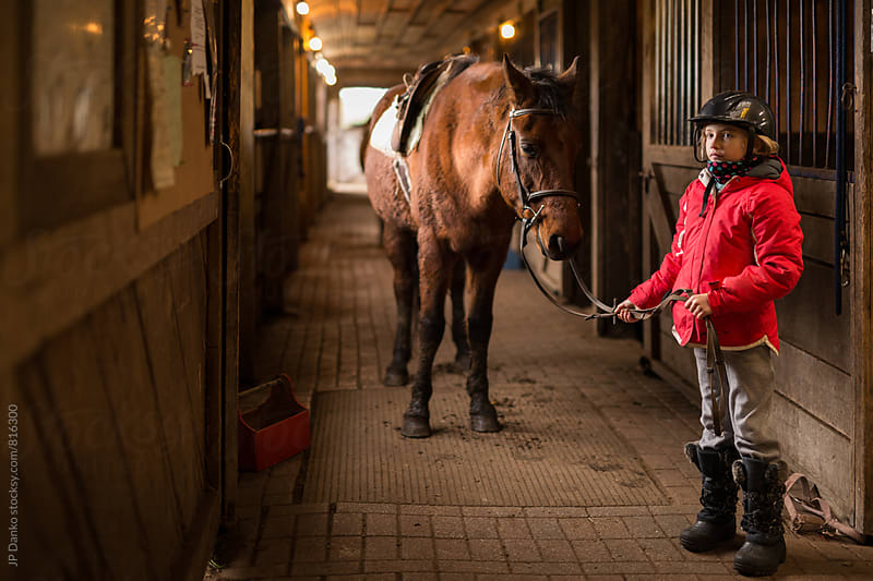 Little Girl Standing With Her Horse at Horesback Riding Lesson in Barn by JP Danko for Stocksy United