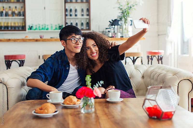 Trendy couple taking selfie having breakfast in a coffee shop. by BONNINSTUDIO for Stocksy United