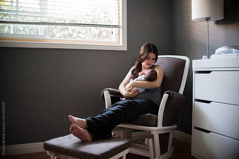 new mother holding her newborn son by Carolyn Brandt for Stocksy United