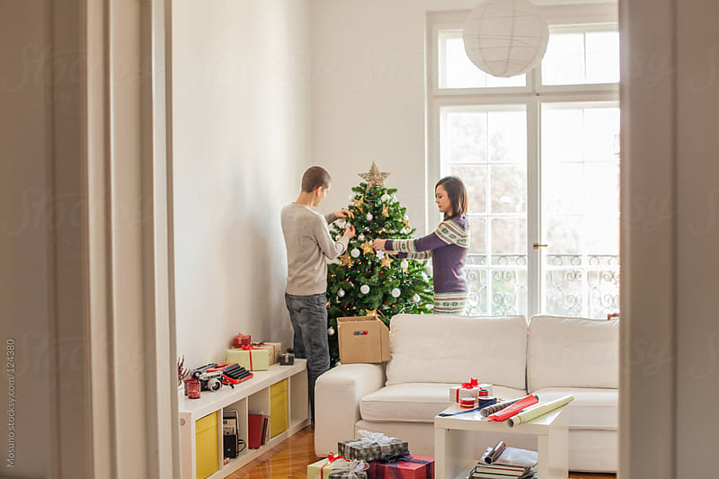 Couple Decorating Christmas Tree by Mosuno for Stocksy United