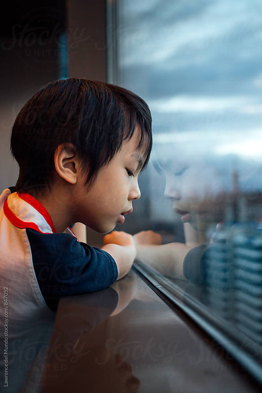Young, little boy looking out the window on a gloomy day by Lawrence del Mundo for Stocksy United