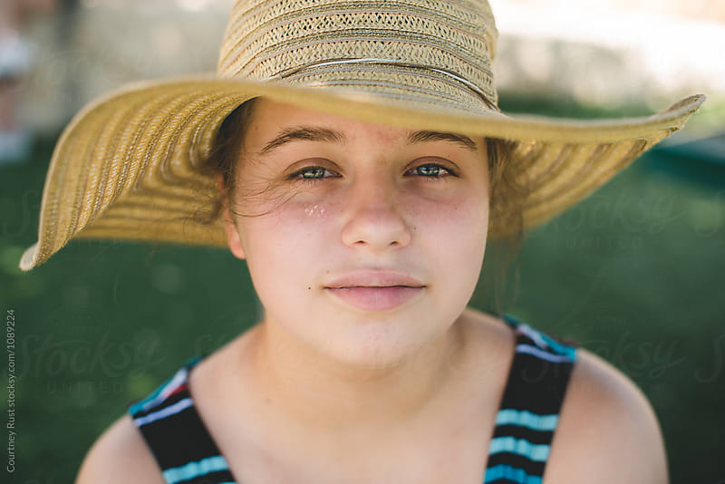 Closeup of teenager in sun or garden hat by Courtney Rust for Stocksy United