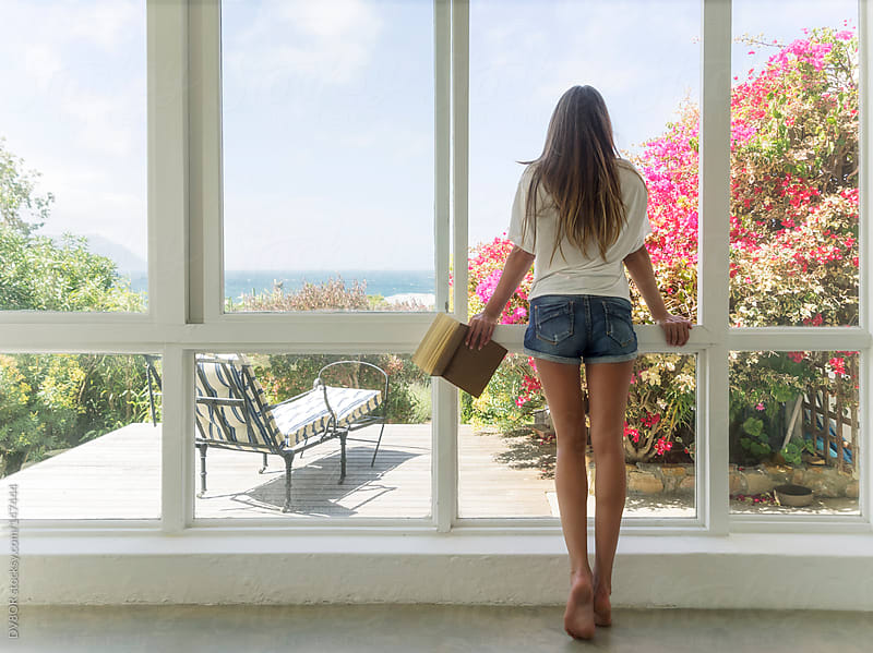 Young beautiful girl leaning in a window overlooking the sea by DV8OR for Stocksy United