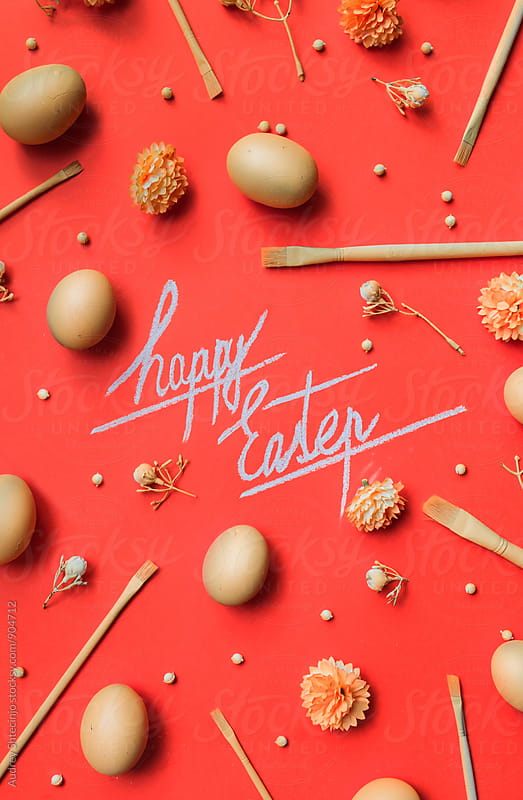 Happy Eastern text with decorations and eggs on red/orange background  by Marko Milanovic for Stocksy United