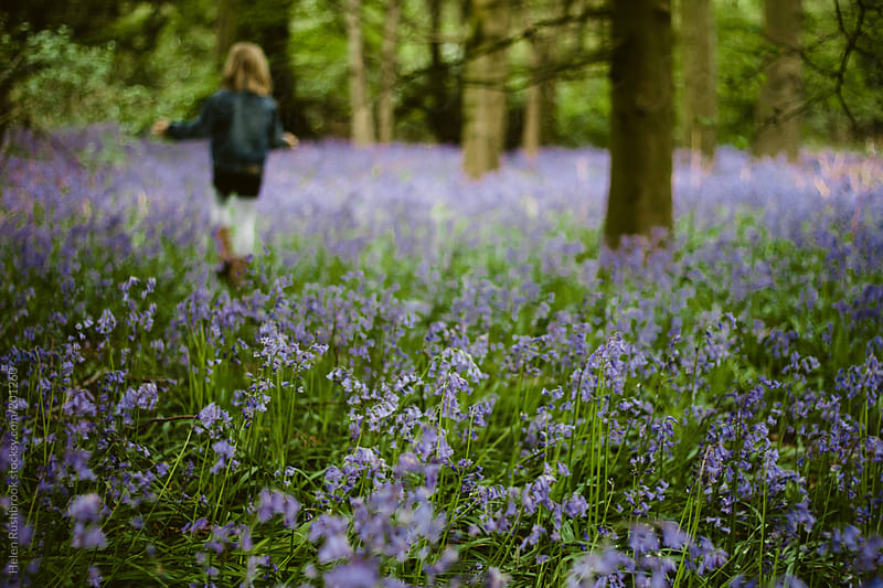 A bluebell wood with a blurry figure in the distance by Helen Rushbrook for Stocksy United
