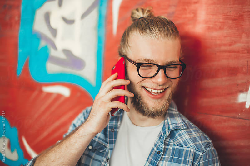 Smiling young man standing against colorful graffiti wall using phone. by Studio Firma for Stocksy United