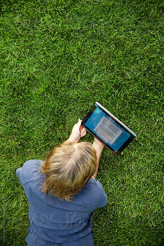 Grass: Woman Reading Book on Digital Tablet by Sean Locke for Stocksy United