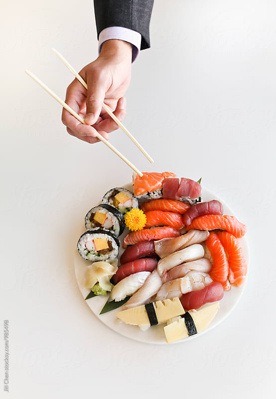 Man in a Suit Reaches for Sushi Platter. by Jill Chen for Stocksy United