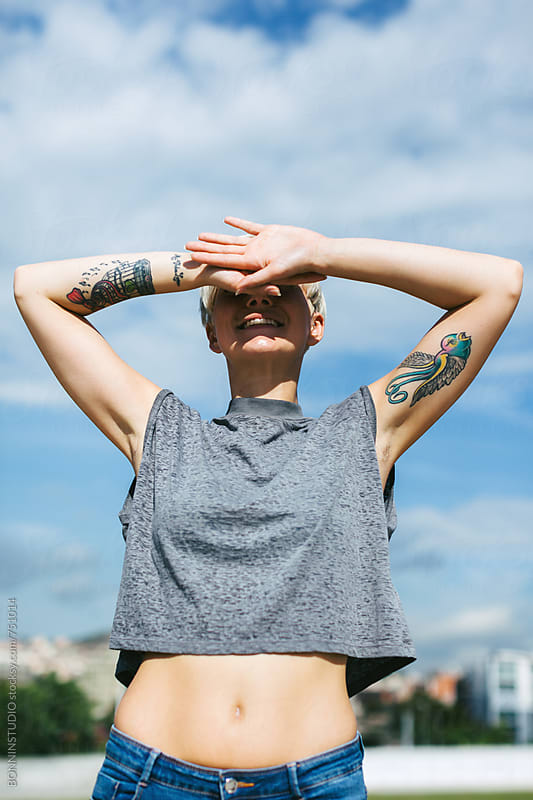 Woman covering her eyes on a sunny day. by BONNINSTUDIO for Stocksy United