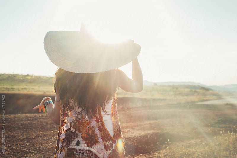 Pretty Woman Wearing Straw Hat from Behind in Warm Afternoon Sunlight by Julien L. Balmer for Stocksy United
