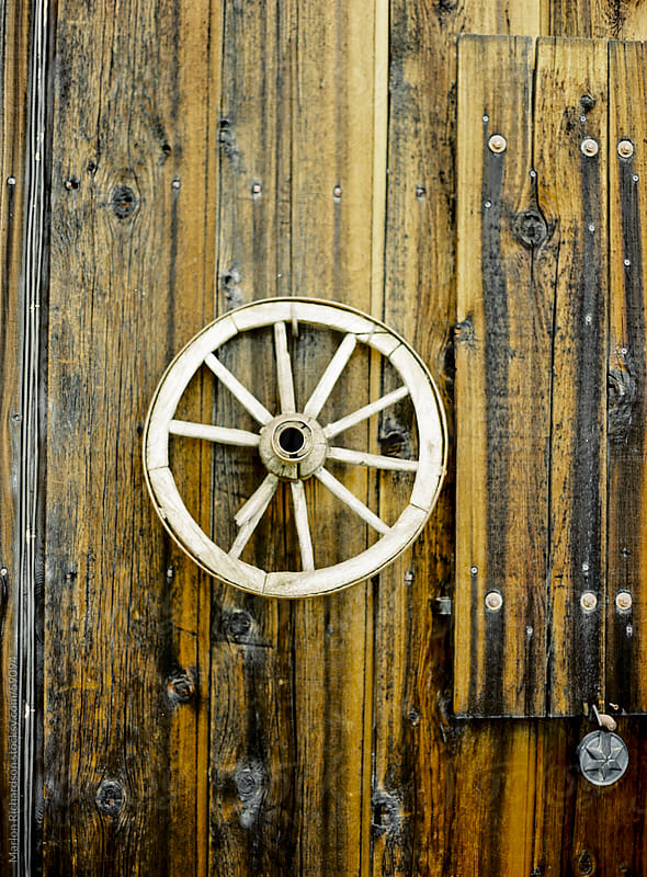 Wagon wheel on a wooden wall by Marlon Richardson for Stocksy United