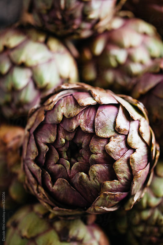 Artichokes on a wooden table by Davide Illini for Stocksy United